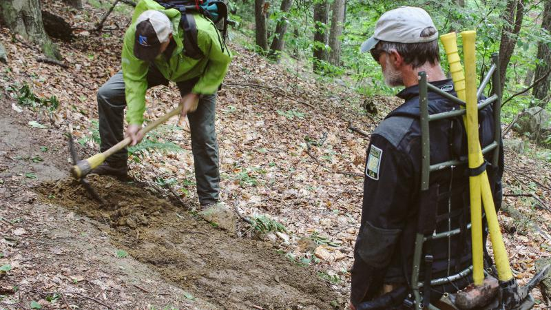 Volunteers working with tools on trail