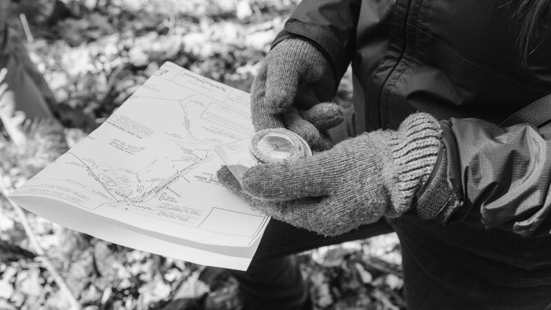 hand holding a compass and property map