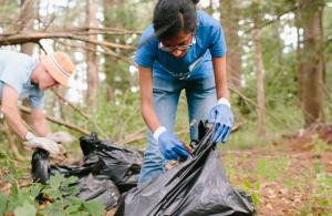 Volunteers cleaning up trash with bags in forest