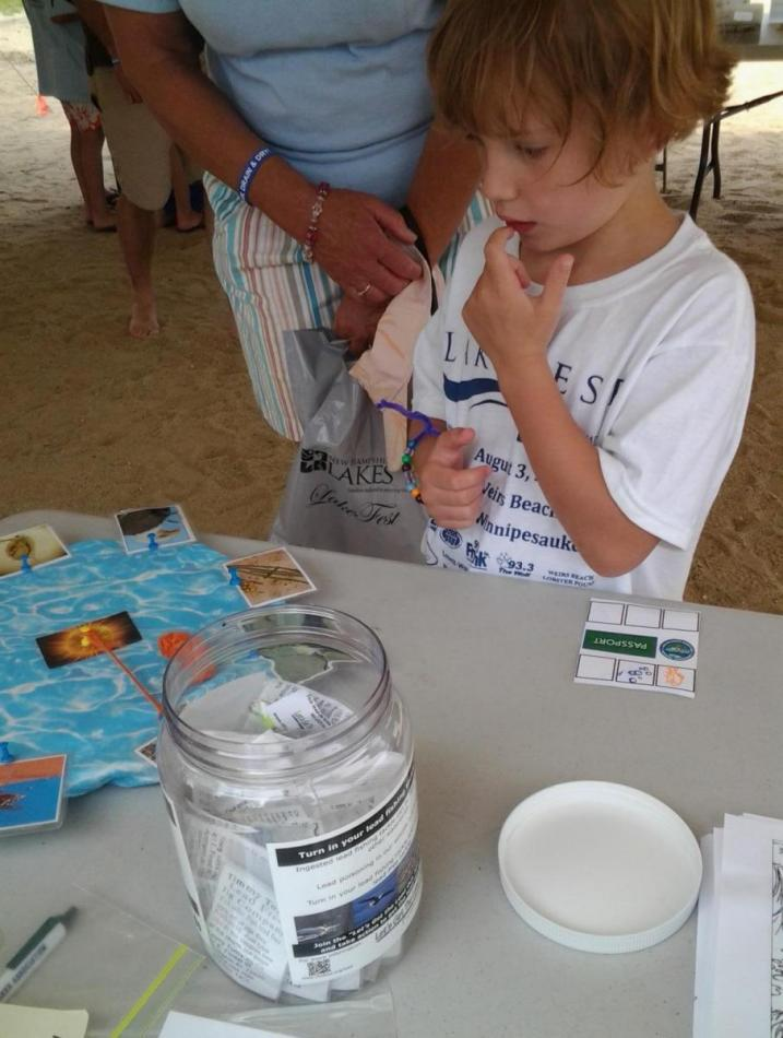 youngster ponders the food web in the Watershed Warriors tent