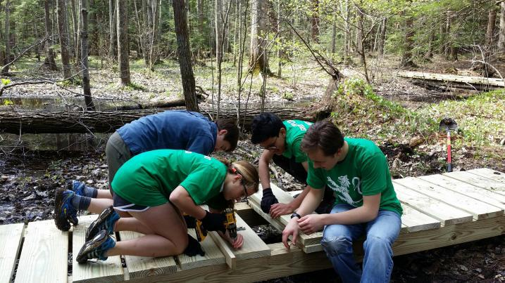 volunteers building a trail bridge