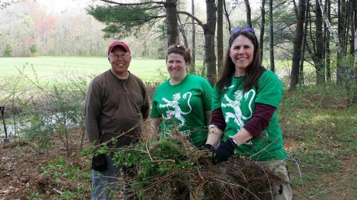 volunteers holding invasive plants