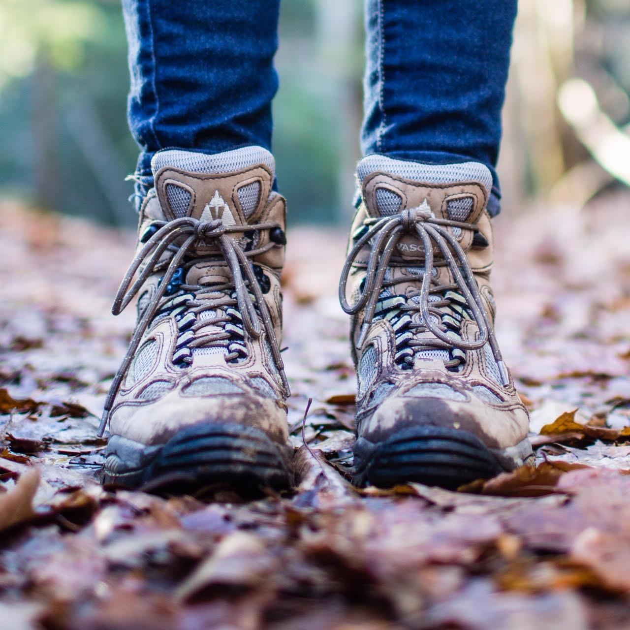 hiking boots on a leaf covered trail